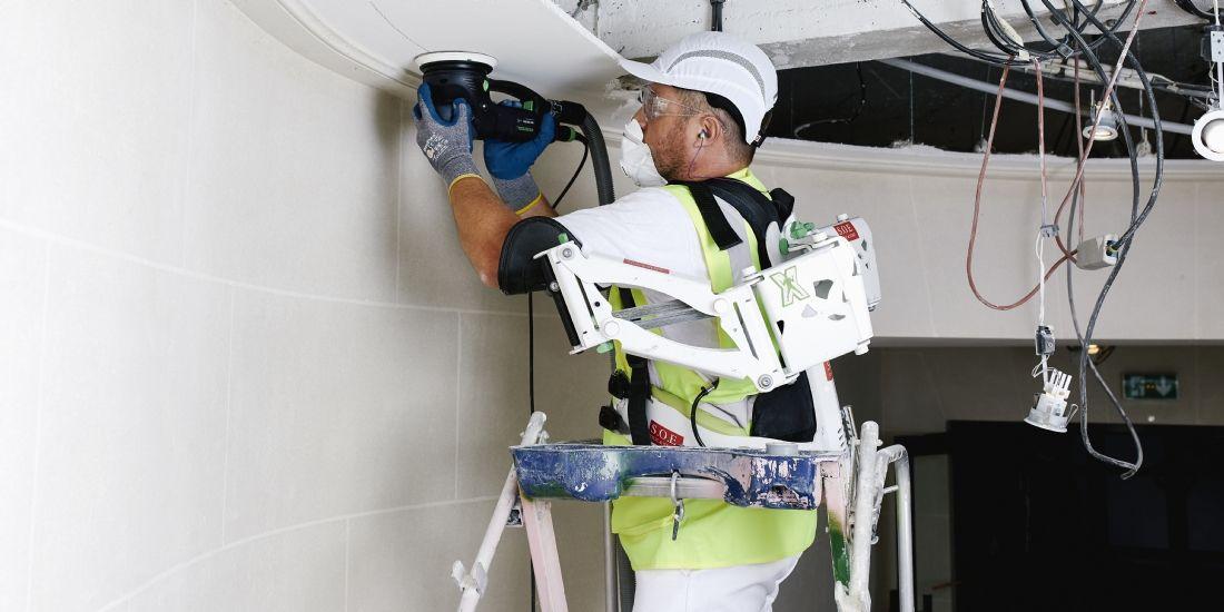 Un salarié de l'entreprise SOE Stuc & Staff équipé d'un exosquelette lors d'une opération de ponçage sur un plafond.